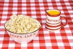 Ciotola di popcorn con la tazza di burro fuso fotografie stock