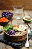 Ciotola di riso con cavolo rosso, le carote, l'avocado, la rucola ed il hummus Fotografie Stock Libere da Diritti