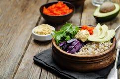 Ciotola di riso con cavolo rosso, le carote, l'avocado, la rucola ed il hummus Fotografia Stock Libera da Diritti