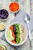 Ciotola di riso con cavolo rosso, le carote, l'avocado, la rucola ed il hummus Immagini Stock Libere da Diritti