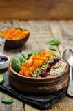 Ciotola di riso con spinaci, la zucca, i semi di zucca e il sau del mirtillo rosso Fotografia Stock Libera da Diritti