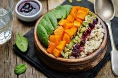 Ciotola di riso con spinaci, la zucca, i semi di zucca e il sau del mirtillo rosso Immagine Stock Libera da Diritti