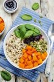 Ciotola di riso con spinaci, la zucca, i semi di zucca e il sau del mirtillo rosso Fotografie Stock