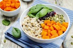 Ciotola di riso con spinaci, la zucca, i semi di zucca e il sau del mirtillo rosso Immagini Stock Libere da Diritti
