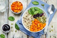 Ciotola di riso con spinaci, la zucca, i semi di zucca e il sau del mirtillo rosso Immagine Stock