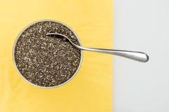 Ciotola di semi secchi di chia con un cucchiaio Immagini Stock