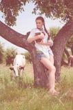 Ciotola di trasporto sorridente del giovane agricoltore di latte fresco Fotografia Stock Libera da Diritti