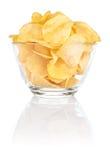 Ciotola di vetro con di patatine fritte del mucchio su bianco Immagini Stock