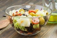 Ciotola di vetro con il pomodoro e le olive della lattuga su legno Fotografia Stock Libera da Diritti