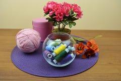 Ciotola di vetro con le bobine dei fili Una palla di filato rosa Immagine Stock Libera da Diritti