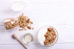 Ciotola di vetro con yogurt greco ed i dadi misti Dieta ricca in proteine vegetariana sana, prima colazione casalinga del granola fotografia stock
