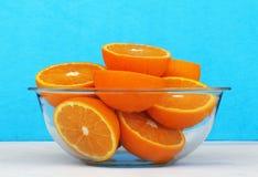 Ciotola di vetro in pieno di spaccatura delle arance in due Immagini Stock Libere da Diritti