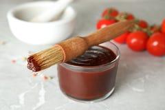 Ciotola di vetro di salsa barbecue con l'unto della spazzola immagini stock
