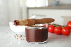Ciotola di vetro di salsa barbecue con l'unto della spazzola immagine stock libera da diritti