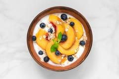Ciotola di yogurt greco con la pesca, l'avena, la menta ed i mirtilli per la prima colazione sana immagine stock