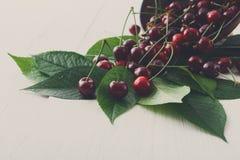 Ciotola fresca delle ciliege su legno bianco Immagine Stock