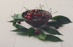 Ciotola fresca delle ciliege su legno bianco Immagini Stock
