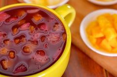 Ciotola gialla con il succo dell'America latina saporito tradizionale della bacca di morada di colada, simbolizzante sangue da qu Immagini Stock