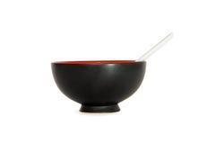 Ciotola nera con la vista laterale del cucchiaio isolata Fotografie Stock