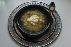 Ciotola nera di minestra e di cucchiaio su un vassoio Immagine Stock Libera da Diritti