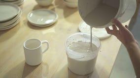 In ciotola in officina il vasaio versa il colore ad acqua per elaborare la tazza dell'argilla archivi video