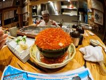 Ciotola in pieno di caviale di color salmone con il cuoco unico nel fondo fotografia stock
