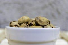 Ciotola in pieno di pistacchi siciliani deliziosi Immagine Stock