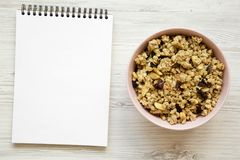 Ciotola rosa di granola della frutta e di blocco note in bianco su fondo di legno bianco, vista superiore fotografie stock libere da diritti