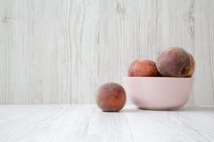 Ciotola rosa di pesche mature su fondo di legno bianco, vista laterale Fotografia Stock