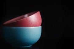 Ciotola rossa e blu su una tavola nera immagine stock
