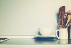 Ciotola rustica bianca e roba differente della cucina, articoli della Tabella su Grey Wall Background Fotografia Stock