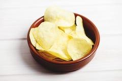 Ciotola rustica con i chip sulla tavola di legno bianca Fotografia Stock