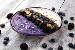 Ciotola sana del frullato della prima colazione con le more ed il granola su fondo rustico immagini stock