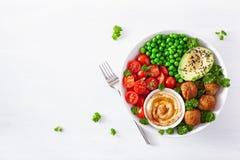 Ciotola sana del pranzo del vegano con i piselli dell'avocado del pomodoro di hummus del falafel fotografie stock