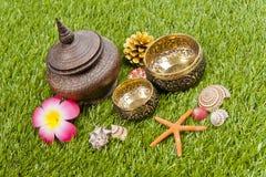 Ciotola tailandese dorata con la bottiglia di legno su erba verde fotografia stock