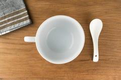 Ciotola, tazza di minestra con il cucchiaio e nakkin sul fondo di legno della tavola Immagini Stock Libere da Diritti