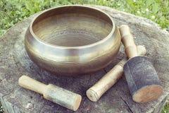 Ciotola tibetana di canto con i magli su un backgroung di legno Fotografia Stock