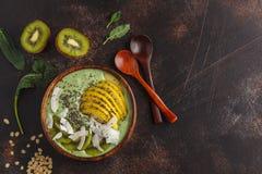 Ciotola verde del frullato del vegano del cavolo con la noce di cocco, il chia, la mela e il kiw fotografie stock