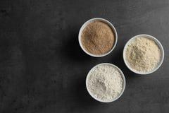 Ciotole con differenti tipi di farine su fondo grigio, vista superiore spazio immagine stock libera da diritti
