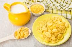 Ciotole con le sabbie di cereale, piattino con i fiocchi di granturco, latte della brocca Fotografia Stock Libera da Diritti