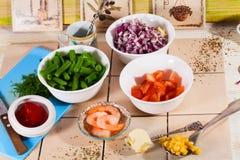 Ciotole, cucina, ricetta, ingrediente, fagiolini, cipolla rossa, mais, pomodori, affettati, mattonelle, interno, natura morta, it Immagine Stock