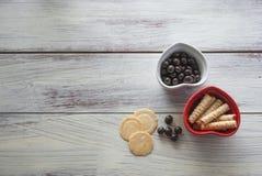 Ciotole di forma del cuore con le caramelle ed i biscotti sulla fine bianca d'annata della tavola su immagine stock libera da diritti