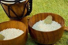 Ciotole di legno con riso e tamtam su verde Immagini Stock Libere da Diritti