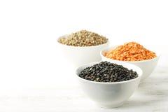 Ciotole di lenticchie secche assortite con le lenticchie rosse, beluga nero l Immagini Stock Libere da Diritti