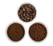Ciotole di vetro con grano, terra e caffè istantaneo su bianco Immagine Stock