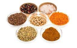 Ciotole differenti con le spezie, i cereali e le erbe su fondo bianco Fotografia Stock