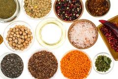 Ciotole differenti con le spezie, i cereali e le erbe su fondo bianco Fotografie Stock