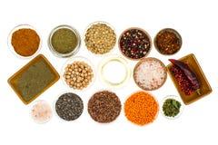 Ciotole differenti con le spezie, i cereali e le erbe su fondo bianco Fotografia Stock Libera da Diritti