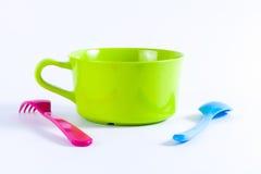 Ciotole variopinte con i cucchiai e forcelle su un fondo bianco Fotografie Stock