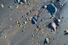 Ciottoli bagnati sulla spiaggia Immagine Stock